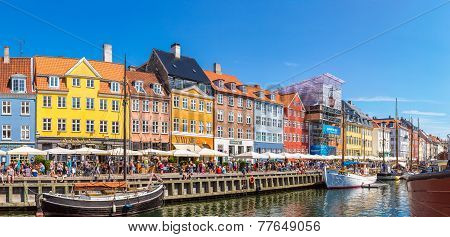 COPENHAGEN DENMARK - JULY 25: Nyhavn district is one of the most famous landmark in Copenhagen. eople enjoy sunny weather in open cafees in Copenhagen on July 25 2014 poster