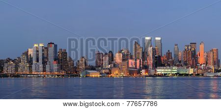 Hudson River waterfront view of New York City Manhattan after sunset with cityscape panorama and light reflection in tranquil blue tone.
