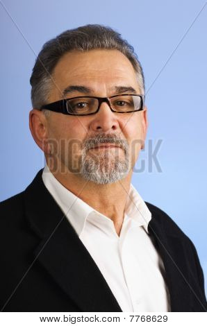 Portrait Of A Serious Mature Man With Glasses Against Blue Background