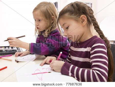Two drawing baby girls, Asian and Caucasian