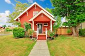 Small coutnryside house exterior in bright red color with white trim. Entrance porch with stairs and white railings poster