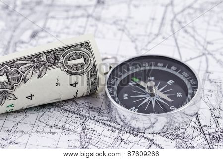 twisted one-dollar bill and a compass lying on a map