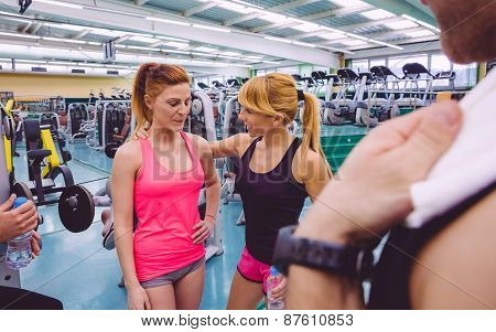 Personal trainer encouraging to sad young woman after a hard training day in the gym poster
