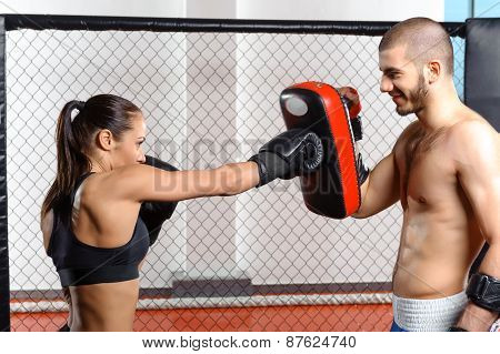Female fighter trains in a fighting cage