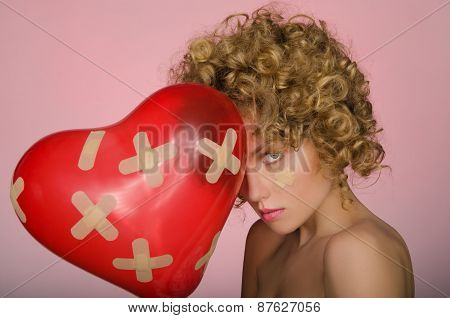 Distressed Young Woman With Ball In Shape Of Heart