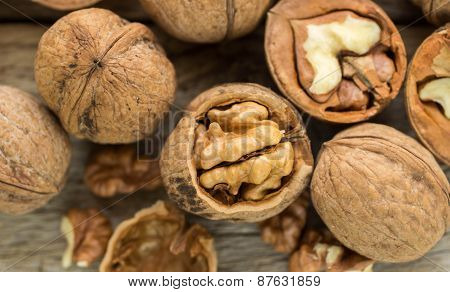 Walnut kernels and whole walnuts on rustic old wooden table. Soft focus poster