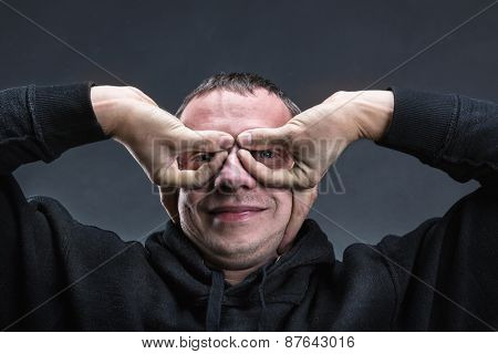 Man with hands like glasses