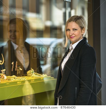 Woman near shop window with jewels.