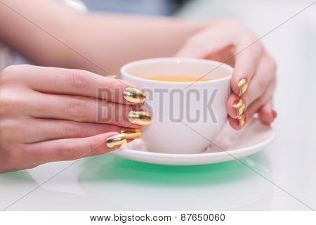 Female Hands With Elegant Gold Manicure Hold A Cup Of Tea