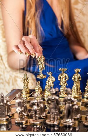 Female Hand With Elegant Gold Manicure Holding Chess Piece