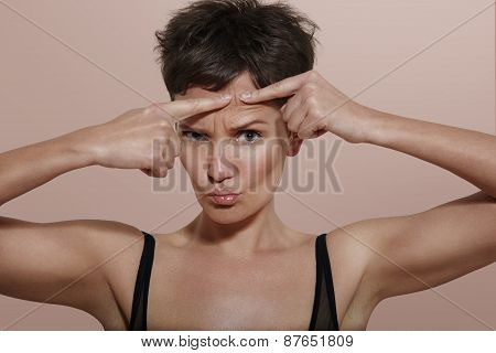 Pretty Girl With Ideal Skin Squeezing Pimple, Beige Back
