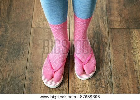 Female feet in socks with pink flip-flops, on floor background