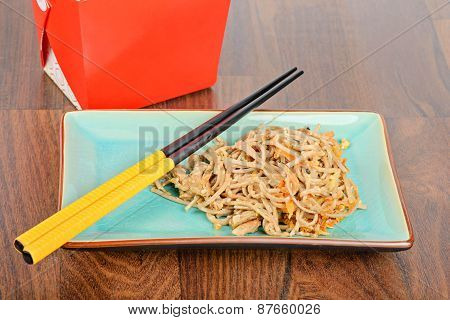 Meat and noodles in blue plate with chopsticks on wooden table. Red take away box on the background. poster