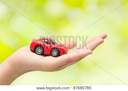 Hand Holding The Model Of Car On Green Background. Symbol Photo For Car Purchase