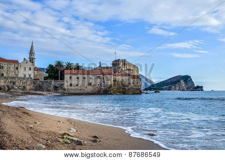 Montenegro. Budva Beach Near Old Town Wall And Fortress In Winte