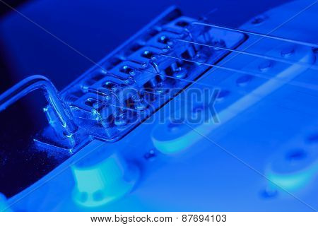 Bridge of an electric guitar with blue light