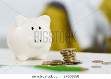Pile Of Different Coins Near White Piggybank