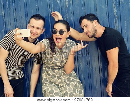 Happy friends taking self photo with smart phone. Selfie, friendship, young adult, happiness, leisure concept. Image toned.