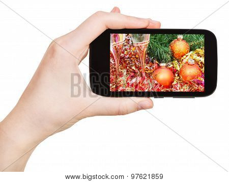 Hand Holds Handphone With Xmas Still Life