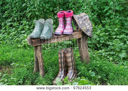 Rubber Shoes For Gardening And Hat Dried On The Bench