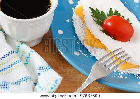 Casabe (bammy beiju bob biju) - flatbread made from cassava (tapioca) with cheese cherry tomato and parsley on blue plate with cup of coffee. Selective focus poster