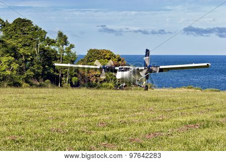 Passenger aircraft landing on grass airstrip on remote island in South Pacific ocean