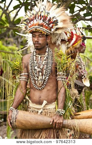 Young Papuan Korafe tribe warrior wearing traditional bird of paradise feather headdress and body de