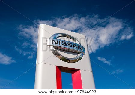 Nissan dealership logo over blue sky