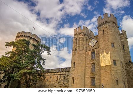 Warwick castle in Warwickshire, England with a dramatic sky in the background. poster