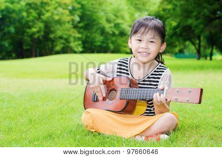 Asian Little Girl Sitting On Grass And Play Ukulele In Park