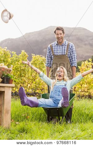 Couple in dungarees pushing a wheelbarrow in the countryside