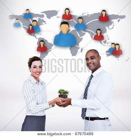 Business colleagues holding plant and looking at camera against grey background