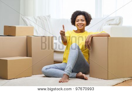 people, moving new place, gesture and repair concept - happy african american young woman with many cardboard boxes sitting on floor and showing thumbs up at home