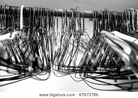 Many several metal wire hangers on pole for hanging clothing in closet storage poster
