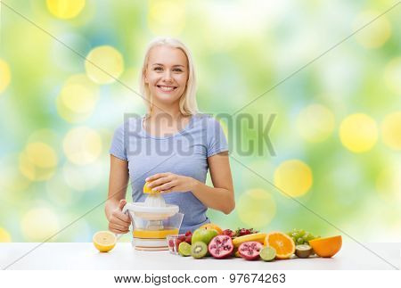 healthy eating, vegetarian food, diet, detox and people concept - smiling woman with squeezer squeezing fruit juice over summer green holidays lights background