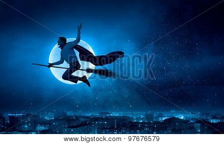 Young businessman flying on broom high in sky poster