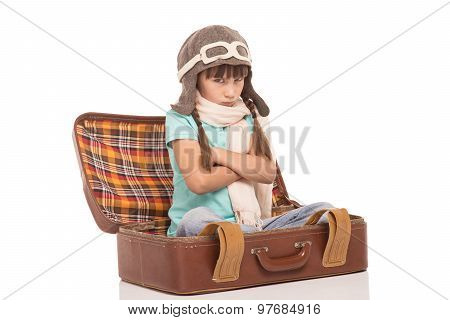 Cute little girl with two braids is isolated on white background. Displeased girl sitting in vintage suitcase, taking offense and wearing like a pilot poster