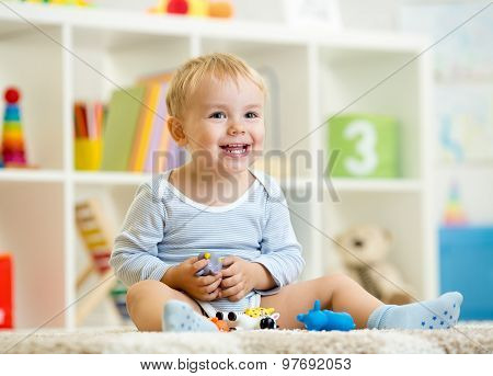 little child boy plays with toys animals