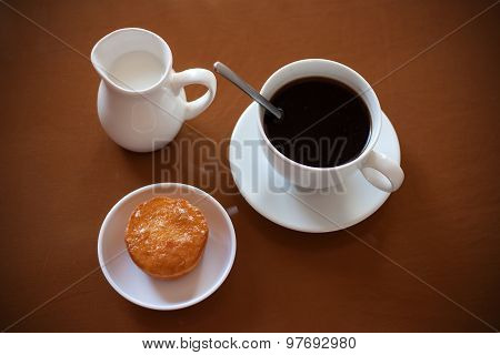 Cup Of Coffee, Creamer Jug And Muffin On Reflective Table
