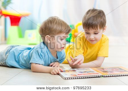 Kids looking at book in playschool or nursery