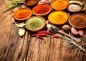 Various herbs and spices on wooden table poster