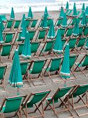 Series of green deckchairs and umbrellas on the beach, Levanto, Italy poster