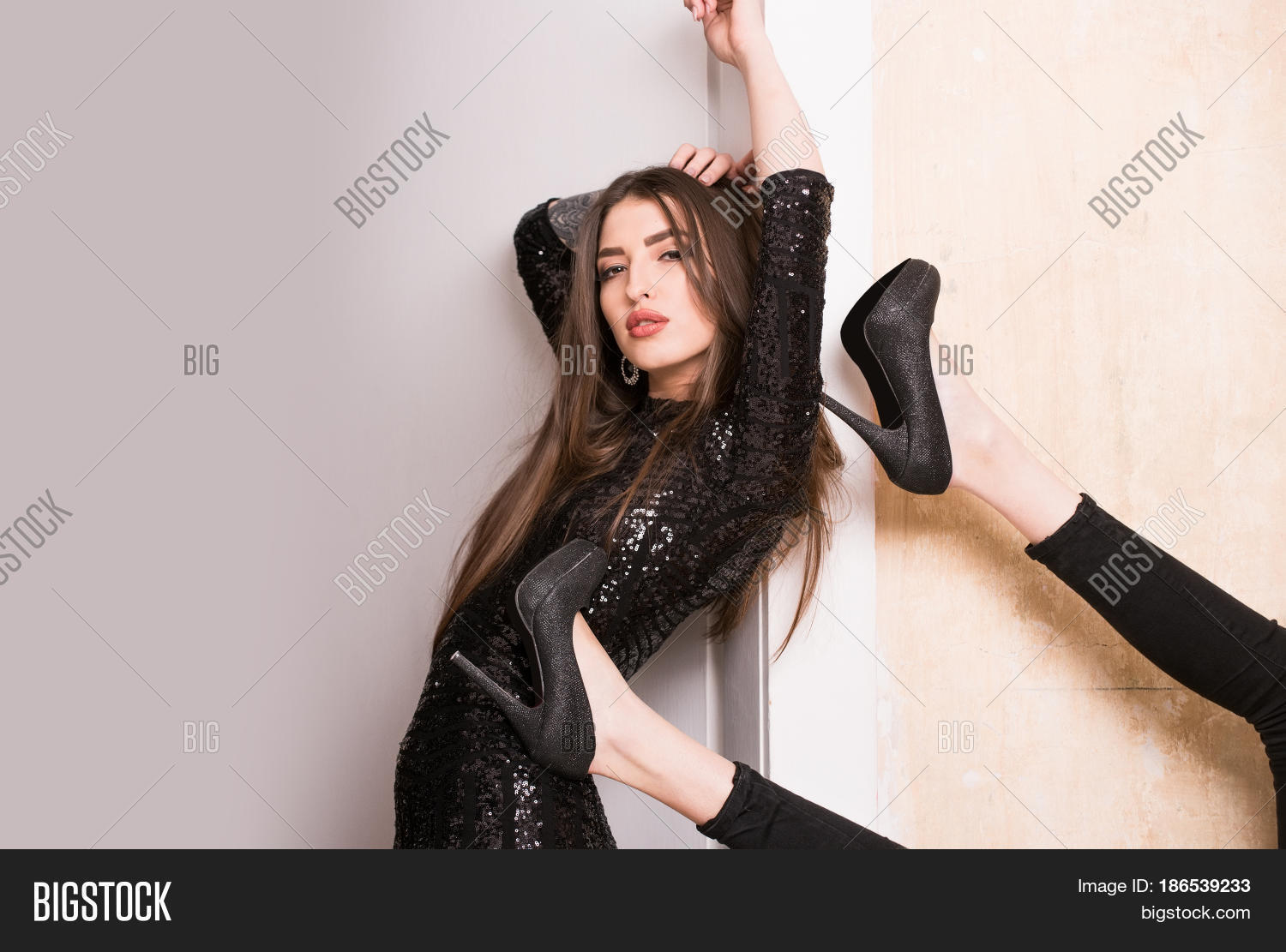 3b367bbf7eb Sexy woman or pretty girl in black sequin dress leaning on white background.  Female legs in elegant fashion shoes on high heels and tights on beige wall.