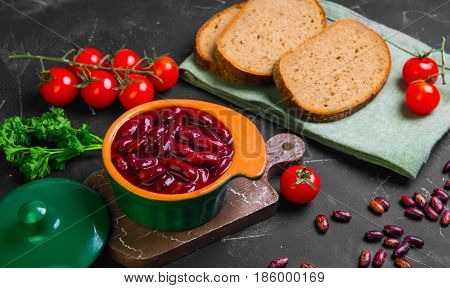 Vegetarian meal red stewed beans in a green ceramic pan. Raw red beans parsley pieces of rye bread cherry tomatoes. Dark black background.