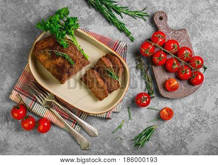 Homemade roast baked meat beef. Ingredients for baked meat beef Cherry tomatoes thyme parsley rosemary. Gray stone background. Top view.
