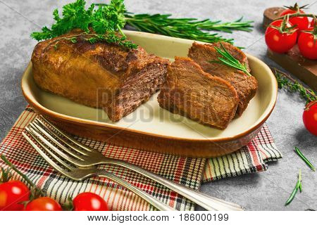 Homemade roast baked meat beef. Ingredients for baked meat beef Cherry tomatoes thyme parsley rosemary. Gray stone background.