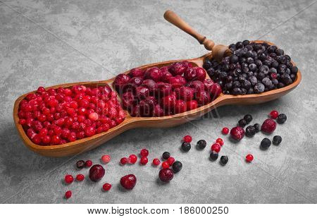 Various frozen berries Red currants blueberries cherries. On gray stone background berries are red blue. A measuring spoon for frozen berries. Empty copy space.