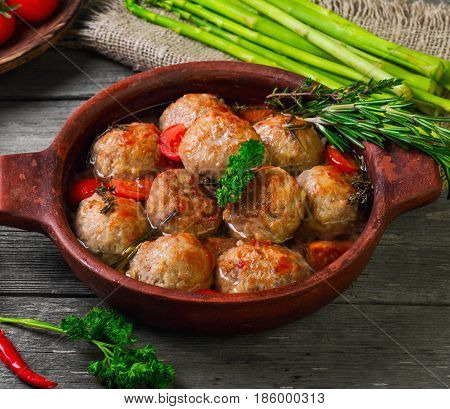 Homemade meatballs noisettes stewed with sauce in the old frying pan. Gray wooden background. Ingredients for meatballs noisettes cherry tomatoes pepper thyme rosemary parsley asparagus.