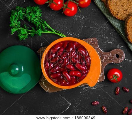 Vegetarian meal red stewed beans in a green ceramic pan. Raw red beans parsley pieces of rye bread cherry tomatoes. Dark black background. Top view