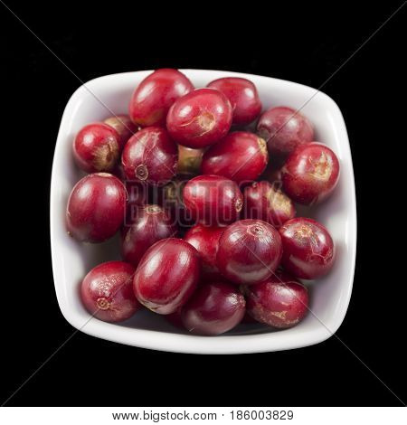 Red and ripe coffee beans in a small dish isolated on a black background